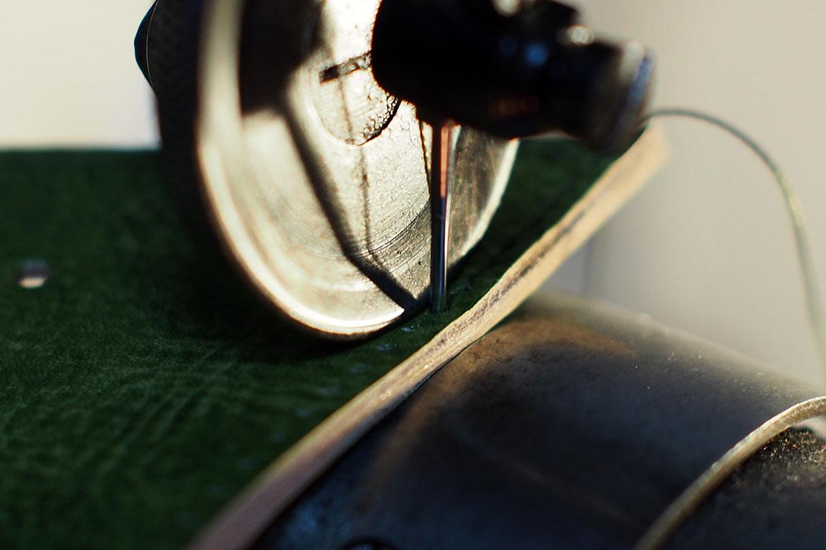 旧式のミシンで革を縫う